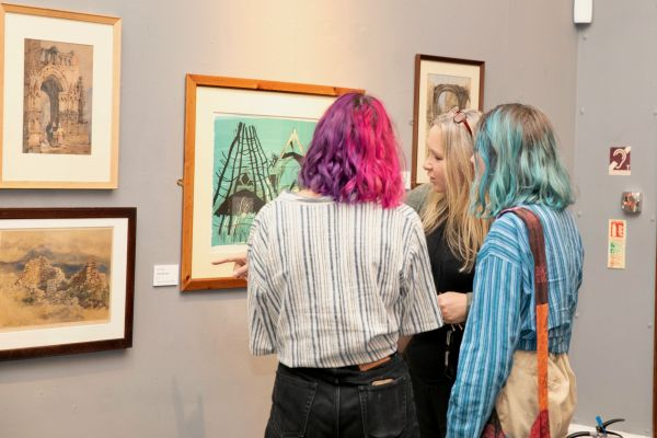 Two girls being guided through an exhibition by a curator in Worcester City Art Gallery & Museum.