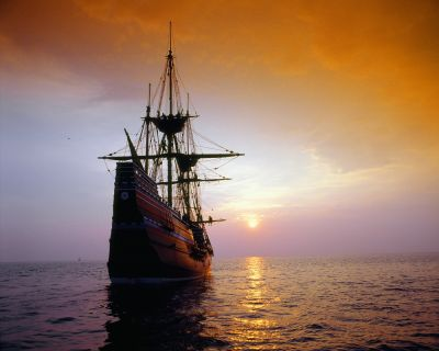 A photo of a 1600s ship sailing into the sunset.