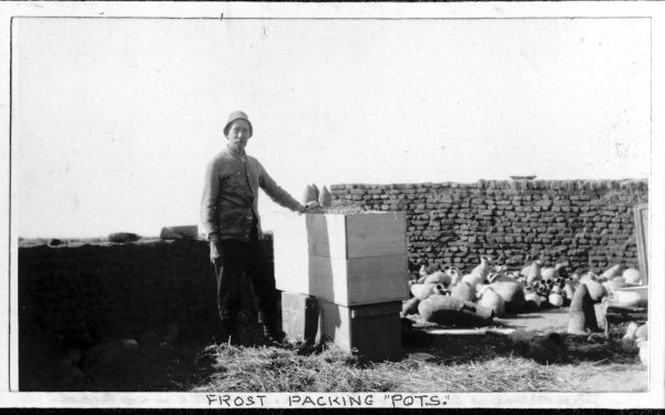 Image of Mr Frost with wooden boxes and a pile of Egyptian pots. A handwritten caption reads 'FROST PACKING
