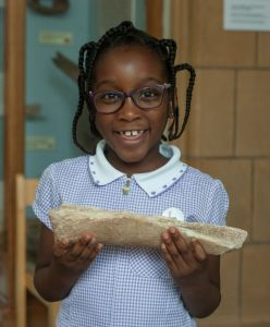 School girl holds fossil in Art Gallery during visit, smiling.