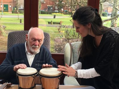 An elderly gentleman plays small drums while a facilitator guides him.