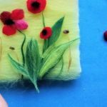 laying down poppy shapes on a wool craft piece